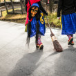Traditional carnival in South Germany - Swabian-Alemannic Fastnacht. Two witches walking down the street. Selective focus on broom. — Stock Photo