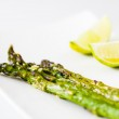 Green asparagus baked with olive oil and garlic. Served with two lime pieces on white plate. — Stock Photo #40552843