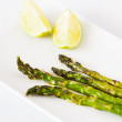 Green asparagus baked with olive oil and garlic. Served with two lime pieces on white plate. — Stock Photo #40552867