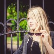 Beautiful blond girl in front of old iron gate. Beautiful green garden in the backyard behind the gate — Stock Photo