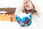 Beautiful blond woman in white fur coat enjoying fresh snow in her hands — Stock Photo