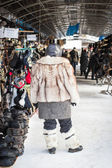 Woman in fur coat standing in the market — Stockfoto