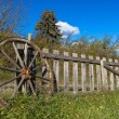 Old wheel and wooden fence — Stock Photo #44297025