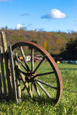 Old wheel and wooden fence — Stock Photo