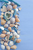 Wooden background with sea shells and hearts — Stock Photo