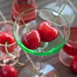 Little green glass with fresh cherries — Stock Photo