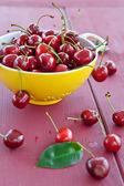 Fresh cherries in a yellow sieve — Stock Photo