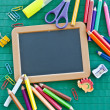 Blank blackboard and colorful office utensils — Photo