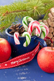 Candy canes in blue cup — Stock Photo