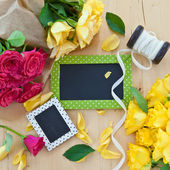 Colorful roses and a little blackboard — Stock Photo