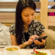 An asian girl is playing with her mobile, ignoring her food — Stock Photo