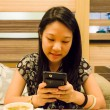 An asian (Thai) girl is playing with her mobile — Stock fotografie