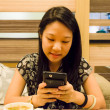 An asian (Thai) girl is playing with her mobile — Photo