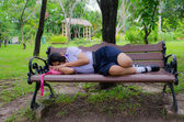 Thai Schoolgirl sleeping alone on the bench, in the park. — Stock Photo