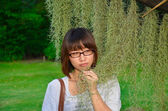 Cute Thai girl examining a Spanish Moss plant — Stock Photo