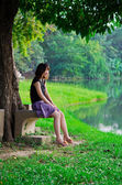 Cute Thai girl is laughing with herself at the river bank — Stock Photo