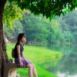 Cute Thai girl is sitting alone under the tree, near the river b — Stock Photo #29203639