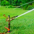 A metal automatic water sprinkler in the field — Stock Photo
