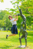 Cute Thai schoolgirl is jumping with a statue in the park — Stock Photo