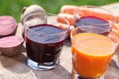 Carrot and beetroot juice on a garden table. — Stock Photo