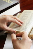 Detail of hands with pen and open Bible — Stockfoto