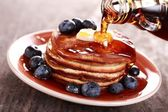 Pouring maple syrup on stack of pancakes — Stock Photo