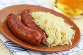 Plate with sausages and pickled cabbage — Stock Photo