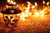 Lantern and Christmas lights burning in dark. — Stock Photo