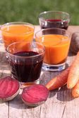 Glass with beetroot and carrot juice on garden table. — Stock Photo