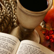 Open Bible, chalice with wine, ear and apple. — Stock Photo #26422481
