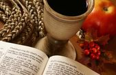 Open Bible, chalice with wine, ear and apple. — Stock Photo