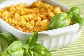 Baking pan with gratin pasta an baasil — Stock Photo