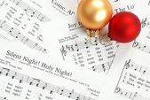 Music notes with Christmas carol and Christmas ornaments — Stock Photo