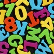 Colorful numbers and letters on black background. — Stock Photo #26572571