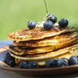 Pouring syrup on pancakes with blueberries. — Stock Photo