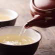Close-up of teapot ant tea pouring into bowl. — Stock Photo