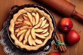 Top view of apple pie, cinnamon sticks and apples — Stock Photo