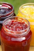 Glass with strawberry, balck currant and peach jam — Stock Photo