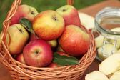 Fresh apple in basket and preserving jar. — Stock Photo
