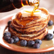 Pouring maple syrup on stack of pancakes. — Stock Photo