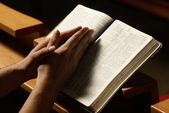 Hands on Holy Bible in prayer at church — Stock Photo