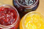 Glass with strawberry, balck currant and peach jam. — Stock Photo