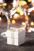 Little gift and wine glass on holiday table. — Stock Photo