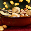 Nutcracker and nuts in a bowl with Christmas lights background. — Stock Photo