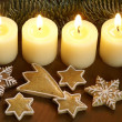 Four candles and gingerbread stars. — Stock Photo