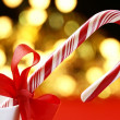 Candy cane with red ribbon on holiday lights background. — Stock Photo