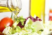 Bottle with pouring olive oil and vegetable salad — Stock Photo