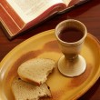Chalice, bread and open Bible on a table. — Stock Photo