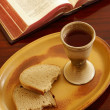 Chalice, bread and open Bible on table. — Stock Photo #27251475