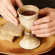Hands with chalice and bread — Stock Photo